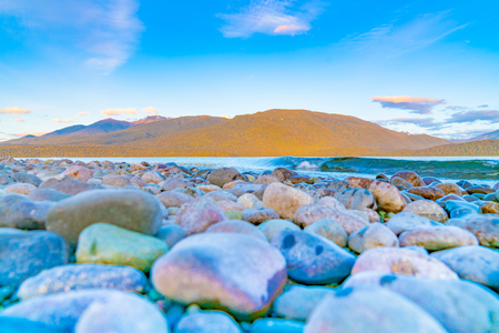 View across colorful stony edge of Lake Te Anau to Murchison Mountains just before sunrise, Milford New Zealand.