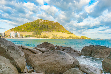 Landmark Mount Maunganui beyond large boulders and across turquoise bay under converging cloud formation Tauranga New Zealand Stock fotó