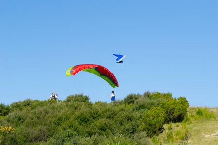 TAURANGA NEW ZEALAND - FEBRUARY 9 2019; Paraglider and hang glider flying in proximity above top of Mount Maunganui. Redakční