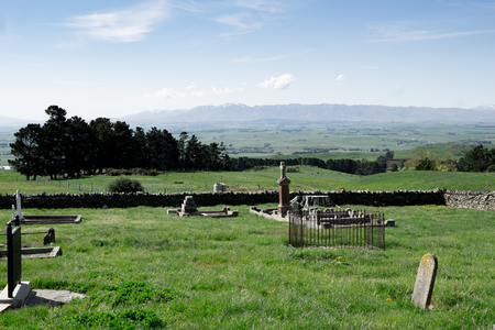 View across old cemetery with broken headstones to expansive rural fields and distant hills in Central Otago New Zealand