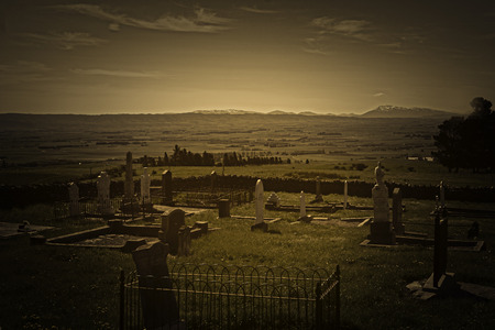 Vintage style image view across old cemetery with broken headstones to expansive rural fields and distant hills in Central Otago New Zealand