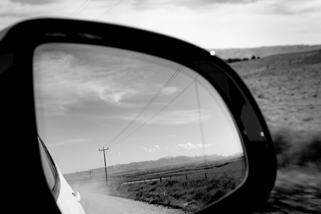 Journey in the rear vision mirror traveling along dry dusty country road Central Otago, New Zealand.