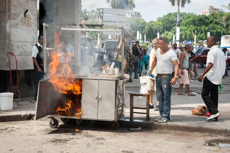 HAVANA CUBA - JULY 7 2012; Food trolley catches fire in city street whiole people staround watching.