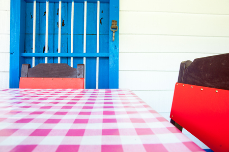 Pink checked table cloth in front blue door close-up background Stock Photo