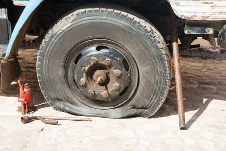 Flat tire on old truck with red jack and tools on ground