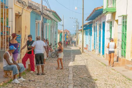 TRINIDAD CUBA JULY 2  2012; People interacting in typical Cuban village street narrow and lined on both sides with homes and doorways. Editorial
