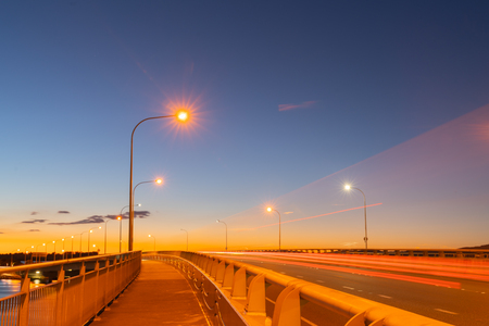Tauranga Harbour Bridge on ramp at dawn with street lights and passing vehicles in long exposure.