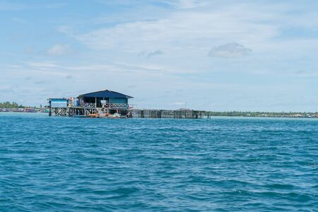 SEMPORNA SABAH - MAY 10 2019; Home and fish-farming base of coast Sabah constructed of timber on poles over water