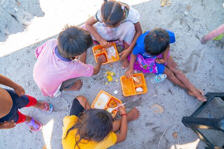 SEMPORNA BORNEO - MAY 11 2019; Hungry children on this tiny idyllic tropical island eagerly grab and eat tourists leftover food. Useful to support articles on poverty, neglect, policy, people,community, housing,