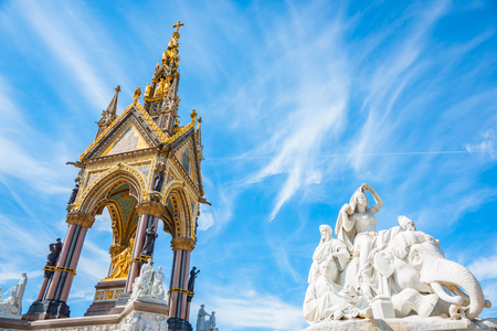 Ornate gold and white Albert Memorial in Kensington Gardens, London with white marble figures and elephant around base designed by Sir Gilbert Scott.