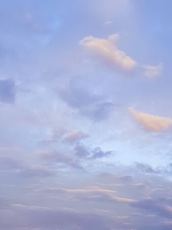 Abstract background of soft blue and orange tones in cloudy sky overhead