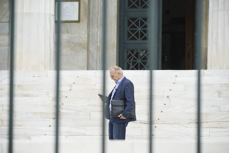 ATHENS GREECE - JULY 15 2019; Through bars of security gate a man dressed in blue holding leather satchel stands on step of Greek Parliament looking at mobile phone.