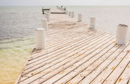 Long pier constructed diagonal planks projecting out into Caribbean