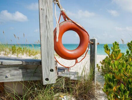Bright orange life bouy hanging on side of beach access on tropical island close up.