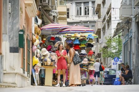 ATHENS GREECE - JULY15 2019; Two women enjoy conversing in front of street vendors hat stand in Plaka area of city.