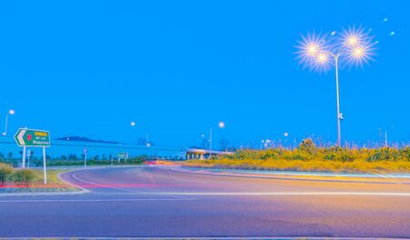 Intersection and roundabout with direction sign to Whakatane, street lights with star burst and light trails from passing cars at Papamoa Tauranga in morning light. 版權商用圖片