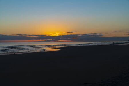 Oceanbeach as sun is on horizon creating golden glow across sea to beach still in dark of morning. Banco de Imagens - 130816792