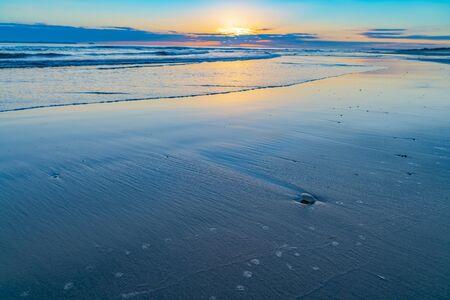Oceanbeach, wie die Sonne am Horizont ist und noch im Dunkeln des Morgens goldenes Leuchten über das Meer zum Strand schafft.