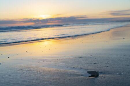 Oceanbeach as sun is on horizon creating golden glow across sea to beach still in dark of morning. Banco de Imagens - 130816797