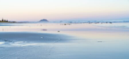 Defocused blurry background image oceanbeach long view in soft tones from Papamoa to Mount Maunganui