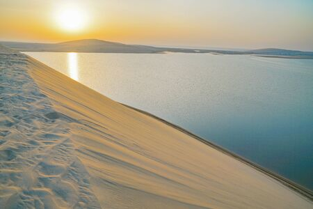 Desert at sunrise, morning glow over dunes and inland sea of the Sealine Desert just out of Doha, Qatar. 版權商用圖片
