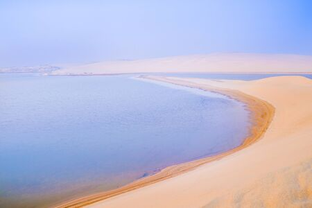Desert at sunrise, golden hue before the sun rises over Sealine Desert dunes and inland lake with its long curving beach.