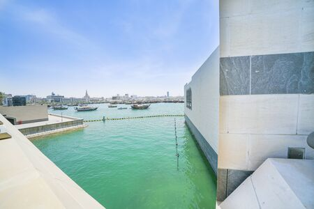 View across Doha harbor to urban skyline from Museum of Islamic Arts interior design and architecture. Banco de Imagens