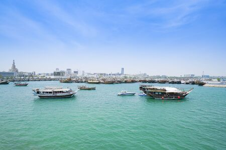 Boats in  harbor Doha with turquoise Persian Gulf water with old town skyline behind