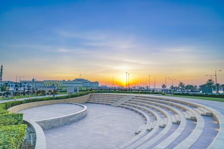 Outdoor event seating in park under sunset glow near The Corniche in old city of Doha at dusk, Qatar.