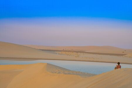 Desert at sunrise, woman sits on dune watching color changes as sun rises over Sealine Desert, Qatar. Stock Photo
