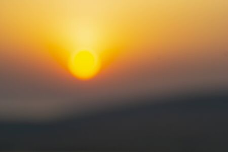 Abstract desert sunrise large defocused golden glow of sun above dersert horizon.
