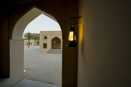 Lanterns glow golden in Arabic design archways as sun gows down in Middle Eastern traditional buildings,