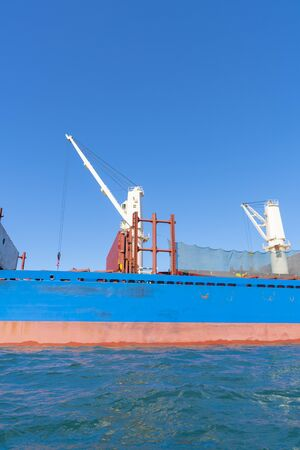 Blue and red hull of ship with white crane against blue sky.