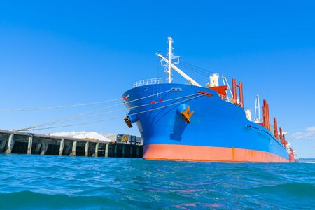 Bright blue and red cargo ship in port standing out against blue sky.