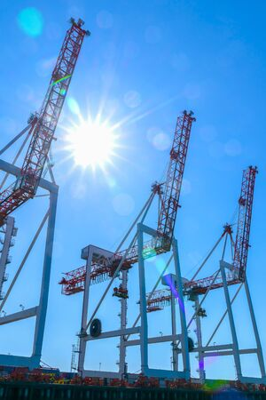 Large container cranes on dock against blue sky back-lit and silhouetted.