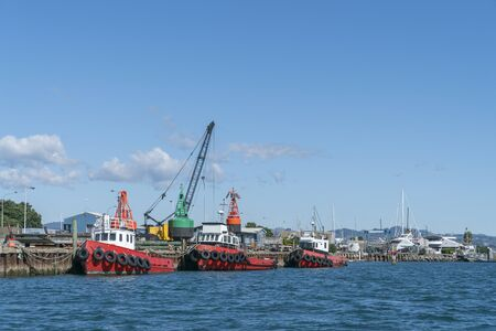 Three red harbour maintenance boats alongside dock with cranes and large buoys behind. Banco de Imagens