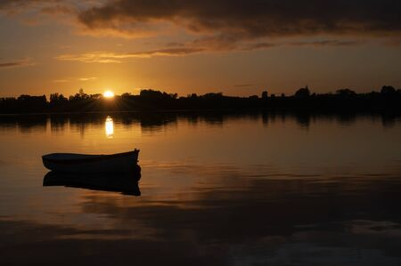 Dark and light contrasts in golden sky before sunrise with small boat on calm water.