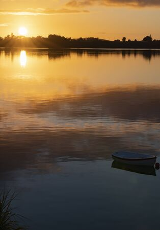Bright and golden sky before sunrise with small boat on calm water.