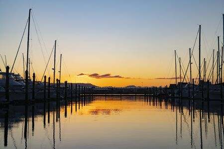 Masts above boats silhouetted against sky colors of setting sun. Banco de Imagens