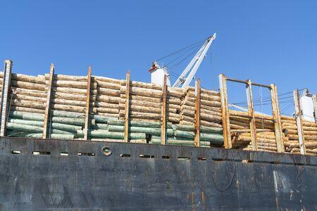 Loaded log ship in port close up.