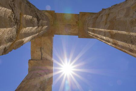 Ancient Temple of Zeus remains of columns towering above into sunburst and lensflare believed to have been constructed from about 500 BC in Nemea in the Peloponesse region Greece.
