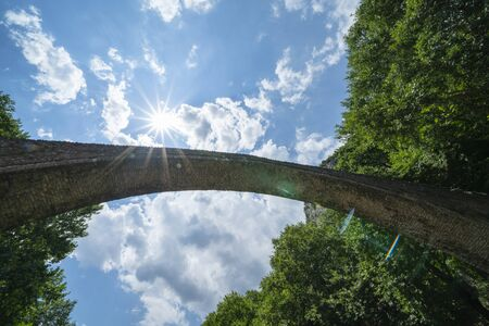 Below historic stone single arch pedestrian bridge looking up to sky at Zagori in mountains in central Greece. Stok Fotoğraf
