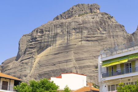 Huge rock formation rises above houses of Meteora Greece.