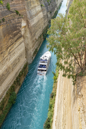 GREECE CORINTH - JULY 17 2019; Large pleasure boat passing through Corinth Canal with its deep sheer sides connecting the Gulf of Corinth with Saronic Gulf in Aegean Sea. Editorial