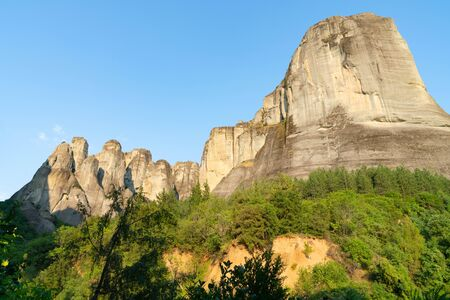 Imposing large rocks with bush covered foothills at Meteora, Greece. 写真素材