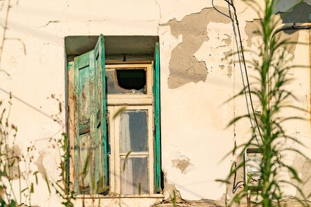 Grungy old wall with broken window and tatty green shutters.