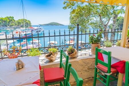 Green chairs with red cushions and tables at a balcony cafe overlooking beautiful Mediterranean sea and boats moored in bay below.