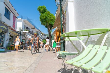 Skiathos Greece - August 4 2019; Man cycles past woman walking along typical narrow Greek Island street