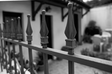 Traditional wrought iron fence  finial in black and white selective focus.