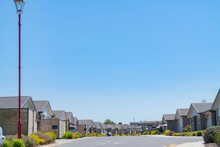 New subdivision street with uniform homes and front gardens lining both sides of street.